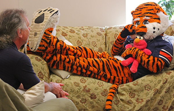 Aubie laying on a couch being counseled